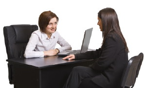photo of two women sitting at a table with computers performing a ux interview