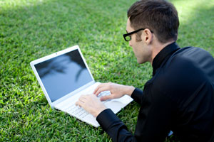 photo of white Guy blogging on a laptop in the park