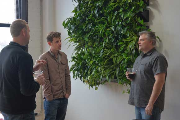 three men talking and drinking beer by a green plant wall