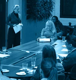 Filtered Photo of woman presenting to a table of listeners