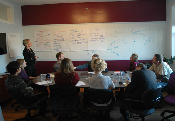 A creative brainstorming session with whiteboard, facilitator, and participants
